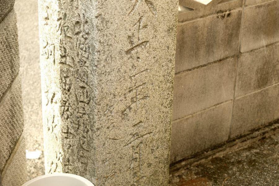 住宅の塀にくいこむ北海道施主の標石 正面右面下部